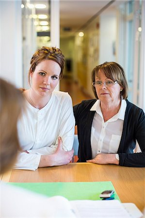 doctor and patient - Mother and daughter looking at female doctor at desk in clinic Stock Photo - Premium Royalty-Free, Code: 698-06966386