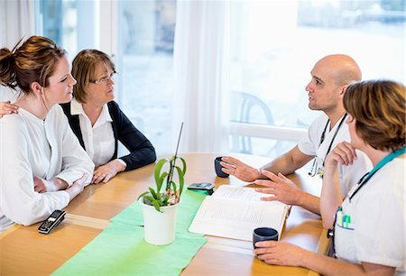 Male and female doctors giving notice to patients at desk in clinic Stock Photo - Premium Royalty-Free, Code: 698-06966387