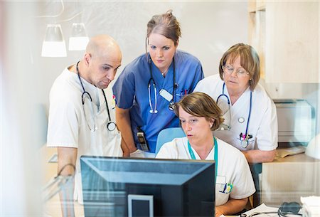 Male and female doctors using computer together in clinic Stock Photo - Premium Royalty-Free, Code: 698-06966380