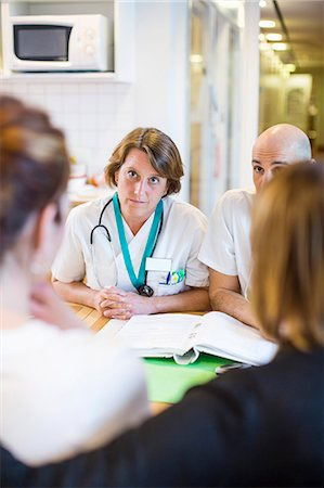 results - Male and female doctors discussing with patients while sitting at desk in clinic Stock Photo - Premium Royalty-Free, Code: 698-06966390