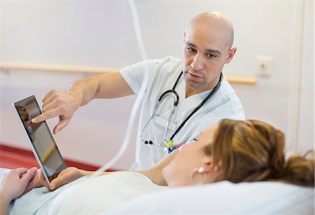 report - Mid adult male doctor showing digital tablet to patient lying on bed in hospital ward Stock Photo - Premium Royalty-Free, Code: 698-06966405
