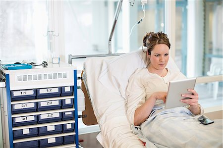 Mid adult female patient using digital tablet while reclining on bed in hospital ward Stock Photo - Premium Royalty-Free, Code: 698-06966409