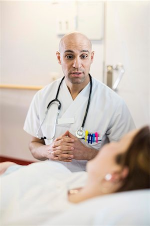report - Mid adult male doctor communicating with female patient lying on bed in hospital ward Stock Photo - Premium Royalty-Free, Code: 698-06966402