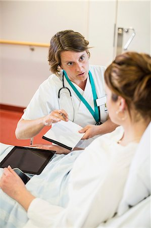report - Female doctor explaining notes to patient in hospital ward Stock Photo - Premium Royalty-Free, Code: 698-06966414