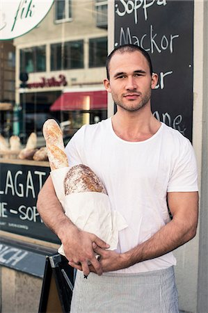 Portrait of male owner holding bread loafs while standing outside bakery Stock Photo - Premium Royalty-Free, Code: 698-06966427