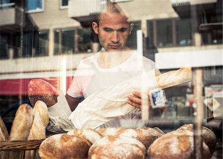 View of mid adult male owner working at bakery through display cabinet Stock Photo - Premium Royalty-Free, Code: 698-06966428