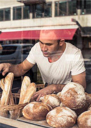 View of male owner working at bakery through display cabinet Stock Photo - Premium Royalty-Free, Code: 698-06966429