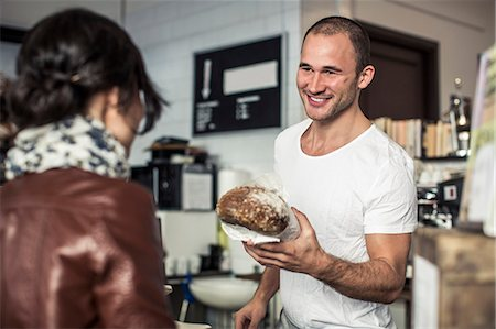 sold sign - Happy young male owner giving bread loaf to customer in bakery Stock Photo - Premium Royalty-Free, Code: 698-06966434