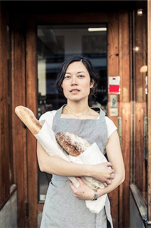 Portrait of confident young female owner holding bread loafs while standing at bakery entrance Stock Photo - Premium Royalty-Free, Code: 698-06966436