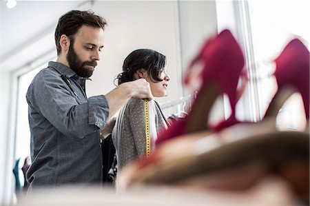 Side view of mid adult male fashion designer measuring woman's shoulder at studio Stock Photo - Premium Royalty-Free, Code: 698-06966447