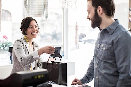 sold sign - Mid adult female design professional giving shopping bag to customer at cash counter in studio Stock Photo - Premium Royalty-Free, Code: 698-06966462