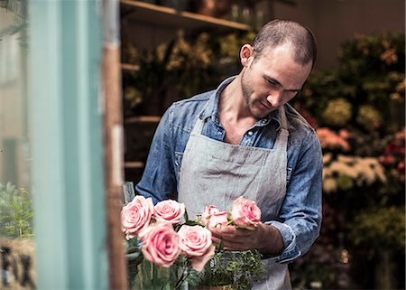 florist - Mid adult male florist analyzing flowers at shop Stock Photo - Premium Royalty-Free, Code: 698-06966474
