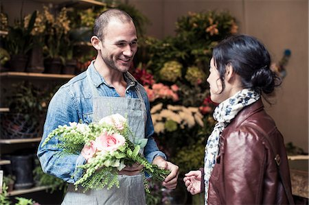 sold sign - Happy male florist giving bouquet of flowers to customer at shop Stock Photo - Premium Royalty-Free, Code: 698-06966477