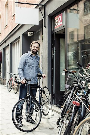 shop - Portrait of happy mid adult male owner standing outside bicycle repair shop Stock Photo - Premium Royalty-Free, Code: 698-06966478