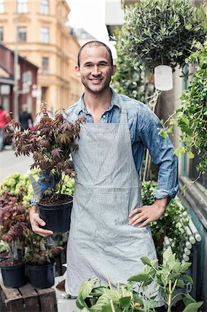 florist - Portrait of confident male florist holding potted plant while standing outside flower shop Stock Photo - Premium Royalty-Free, Code: 698-06966471