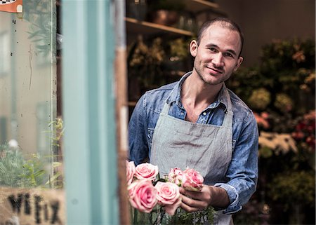 florist - Portrait of happy male florist holding flowers while working at shop Stock Photo - Premium Royalty-Free, Code: 698-06966473