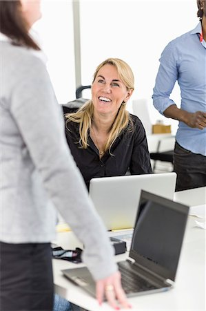 focus on background - Happy mid adult businesswoman looking at colleague at desk in office Stock Photo - Premium Royalty-Free, Code: 698-06966518