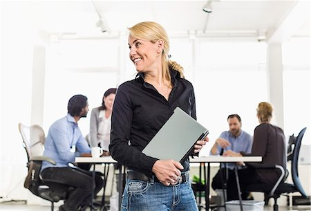 five - Mature businesswoman looking away while holding laptop with colleagues sitting at desk in background Stock Photo - Premium Royalty-Free, Code: 698-06966513