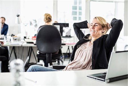 Relaxed mid adult businesswoman looking away while reclining at desk in office Stock Photo - Premium Royalty-Free, Code: 698-06966530