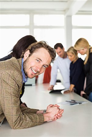 Portrait of happy mid adult businessman leaning on desk with colleagues in background Stock Photo - Premium Royalty-Free, Code: 698-06966544