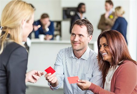 Business people giving business card to woman in office Stock Photo - Premium Royalty-Free, Code: 698-06966547