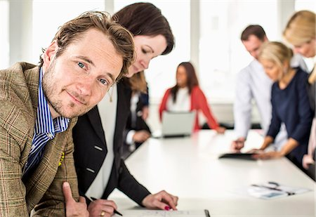 Portrait of mid adult businessman leaning at desk with colleagues working in background Stock Photo - Premium Royalty-Free, Code: 698-06966543