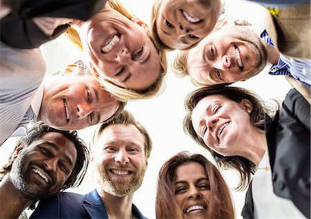 Directly below shot of business people forming huddle against clear sky Stock Photo - Premium Royalty-Free, Code: 698-06966559
