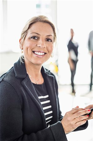 Portrait of mid adult businesswoman holding mobile phone in office Stock Photo - Premium Royalty-Free, Code: 698-06966568