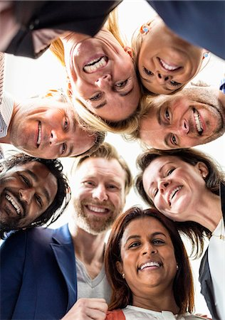 person - Directly below shot of multi-ethnic business people forming huddle Stock Photo - Premium Royalty-Free, Code: 698-06966560