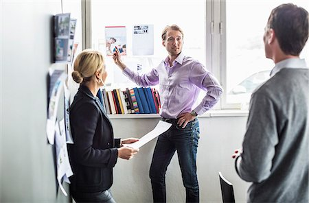 Business colleagues discussing over photograph in office Stock Photo - Premium Royalty-Free, Code: 698-06966588