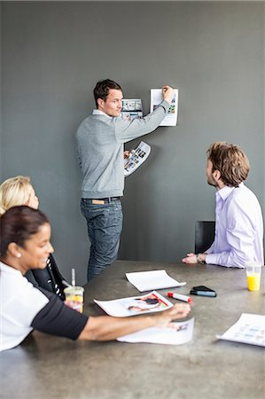 presentation (displaying) - Mid adult businessman sticking photograph on wall while colleagues looking at him in office Stock Photo - Premium Royalty-Free, Code: 698-06966580