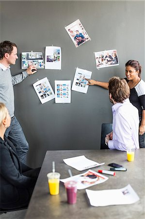 displaying - Mid adult businesswoman giving presentation over photograph to colleagues in office Stock Photo - Premium Royalty-Free, Code: 698-06966581
