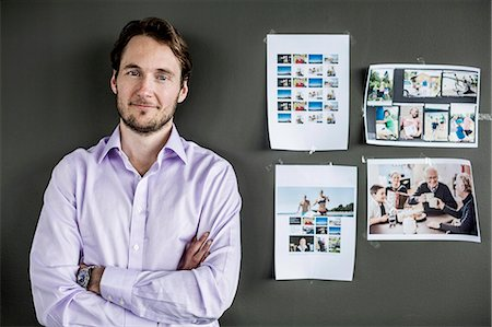 portrait smile caucasian one - Portrait of mid adult businessman standing arms crossed against wall in office Stock Photo - Premium Royalty-Free, Code: 698-06966599