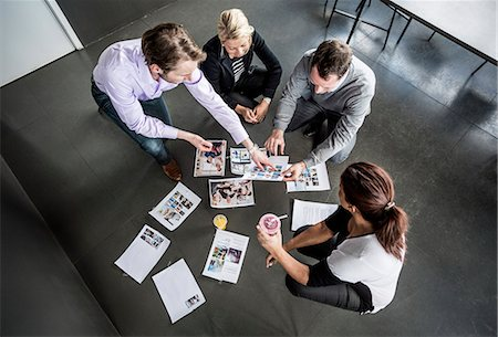 displaying - High angle view of business colleagues working with photographs in office Stock Photo - Premium Royalty-Free, Code: 698-06966605