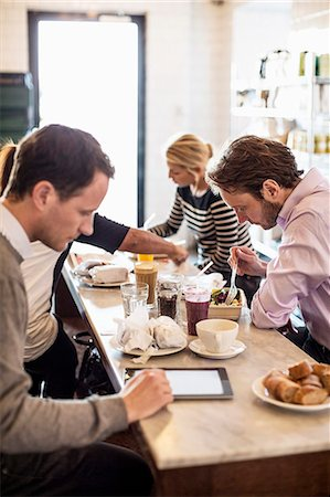 Mid adult businessman using digital tablet with colleagues having breakfast at restaurant table Stock Photo - Premium Royalty-Free, Code: 698-06966607