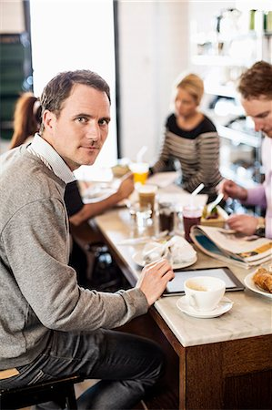 europe coffee shop - Portrait of mid adult businessman with colleagues having breakfast in office restaurant Stock Photo - Premium Royalty-Free, Code: 698-06966609