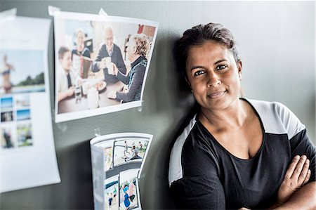 focus on background - Portrait of businesswoman with arms crossed leaning on wall in office Stock Photo - Premium Royalty-Free, Code: 698-06966601