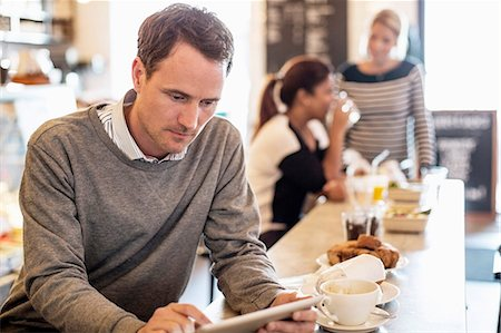 Mid adult businessman using digital tablet at restaurant table with colleagues in background Stock Photo - Premium Royalty-Free, Code: 698-06966617