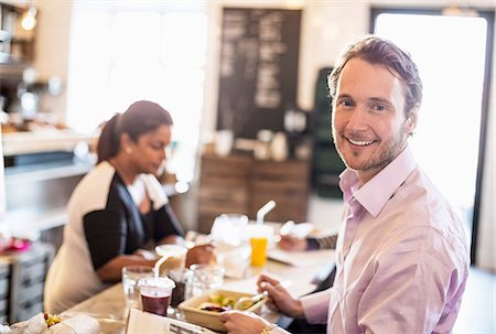 europe coffee shop - Side view portrait of mid adult businessman having breakfast with colleague in background at office restaurant Stock Photo - Premium Royalty-Free, Code: 698-06966610