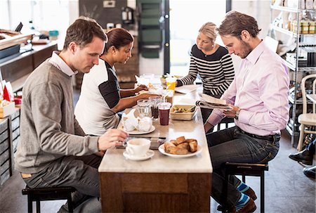 Businessmen and businesswomen having breakfast together in office restaurant Stock Photo - Premium Royalty-Free, Code: 698-06966611