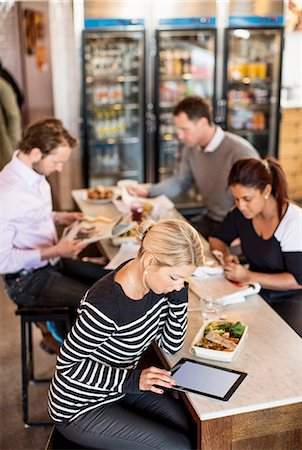 europe coffee shop - High angle view of mid adult businesswoman using digital tablet with colleagues in background at office restaurant table Stock Photo - Premium Royalty-Free, Code: 698-06966612