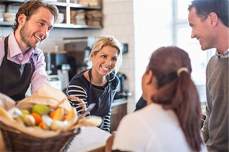 small business - Male and female owner attending customers at counter in restaurant Stock Photo - Premium Royalty-Free, Code: 698-06966629