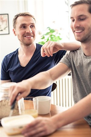 Happy homosexual couple having breakfast together while sitting at table Stock Photo - Premium Royalty-Free, Code: 698-06966636