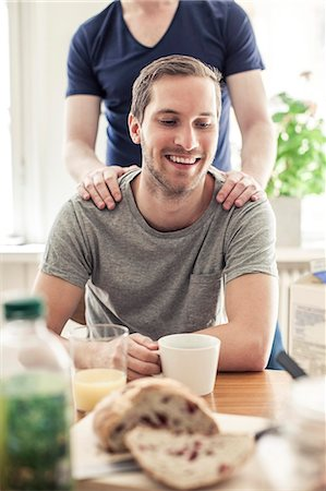Happy gay man having coffee while partner standing behind him at table in home Stock Photo - Premium Royalty-Free, Code: 698-06966638