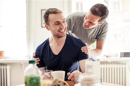 Young gay man looking at partner while having breakfast in house Stock Photo - Premium Royalty-Free, Code: 698-06966639