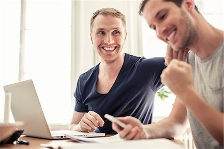 Happy loving homosexual couple with laptop siting at table in home Stock Photo - Premium Royalty-Free, Code: 698-06966649