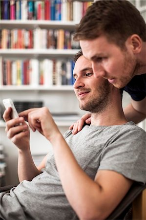 Gay men using mobile phone together at home Stock Photo - Premium Royalty-Free, Code: 698-06966656