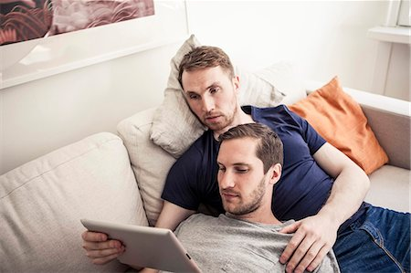 Young homosexual using digital tablet together while relaxing on sofa at home Stock Photo - Premium Royalty-Free, Code: 698-06966666