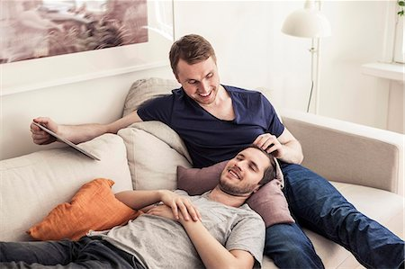 Young gay man holding digital tablet while partner sleeping on lap at home Stock Photo - Premium Royalty-Free, Code: 698-06966668