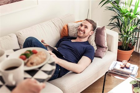 Cropped image of young gay man bringing breakfast for partner lying on sofa Stock Photo - Premium Royalty-Free, Code: 698-06966669